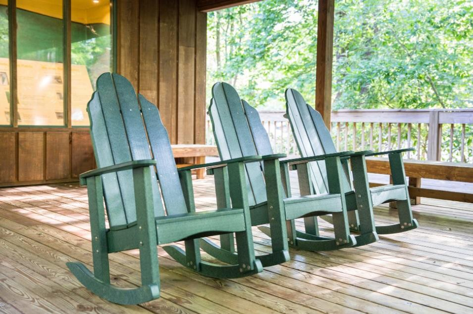 3 green rocking chairs sit underneath wooden pavilion