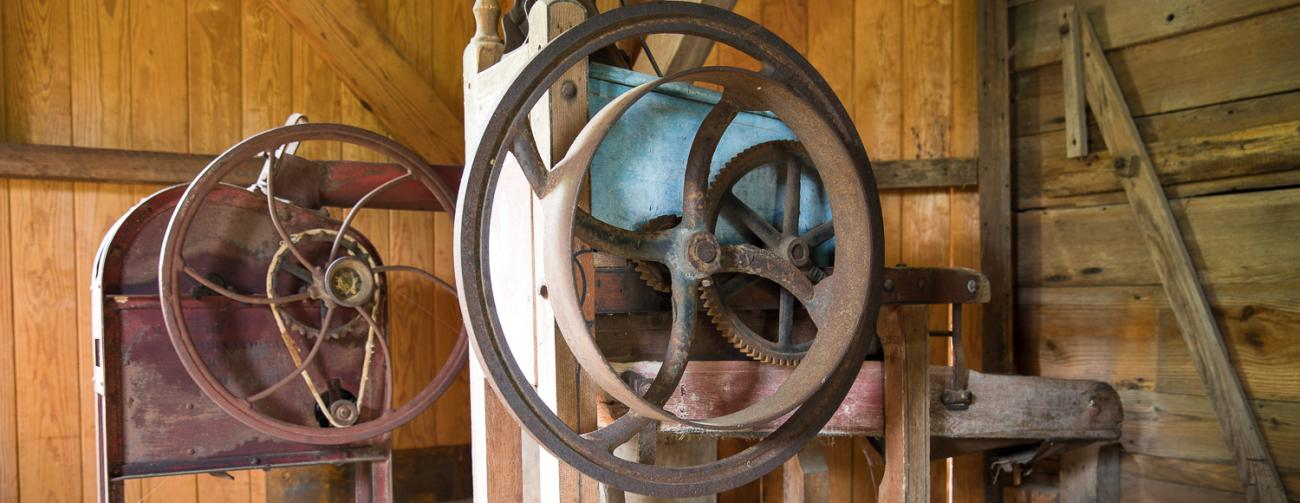 two old rusted wheel and axle machines inside old wooden mill building