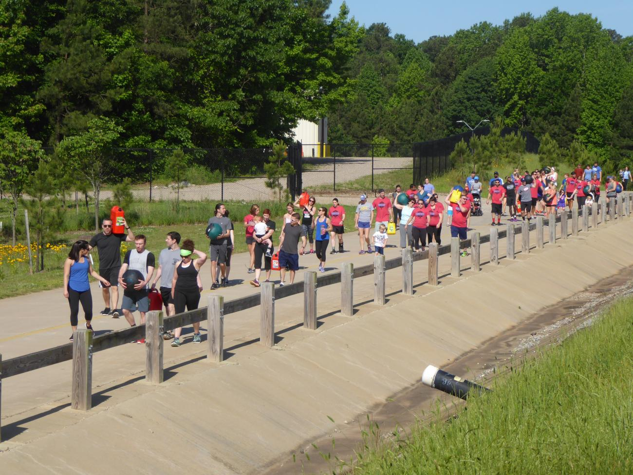 Event at Green Hills featuring a large group of people carrying items along the concrete road.