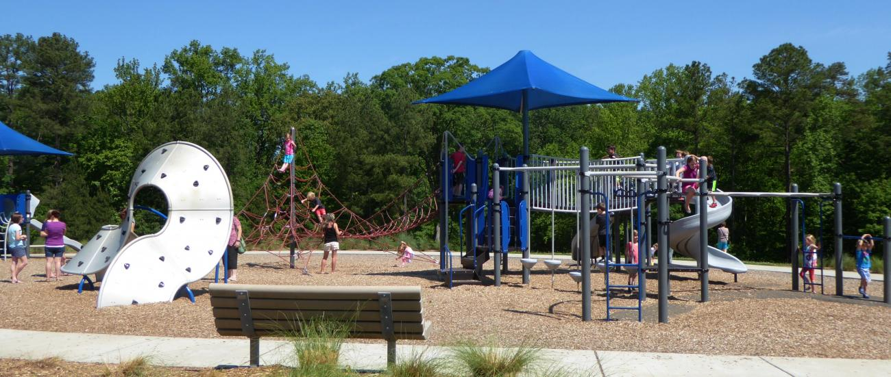 Children playing on the playground under sunny skies while adults supervise.
