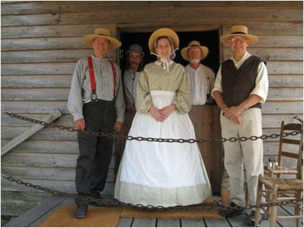 Group of costumed volunteers stand together in front of old wooden mill