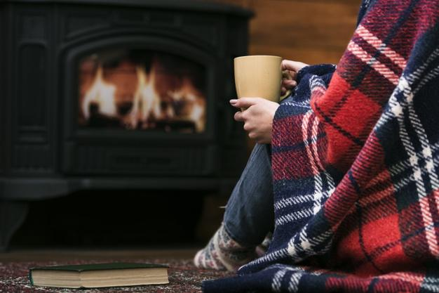 Woman sitting in front of a lit fireplace.