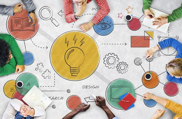 view from above, people around a table with idea, tech and innovation-related illustrations