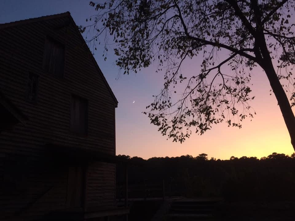 silhouette of mill building at sunset