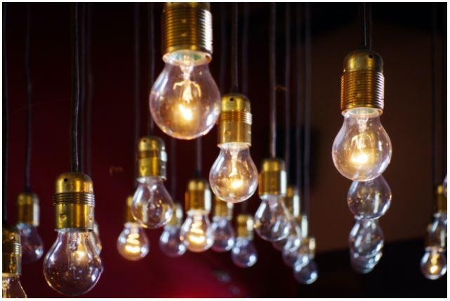 photo of several lit lightbulbs hanging with a dark background