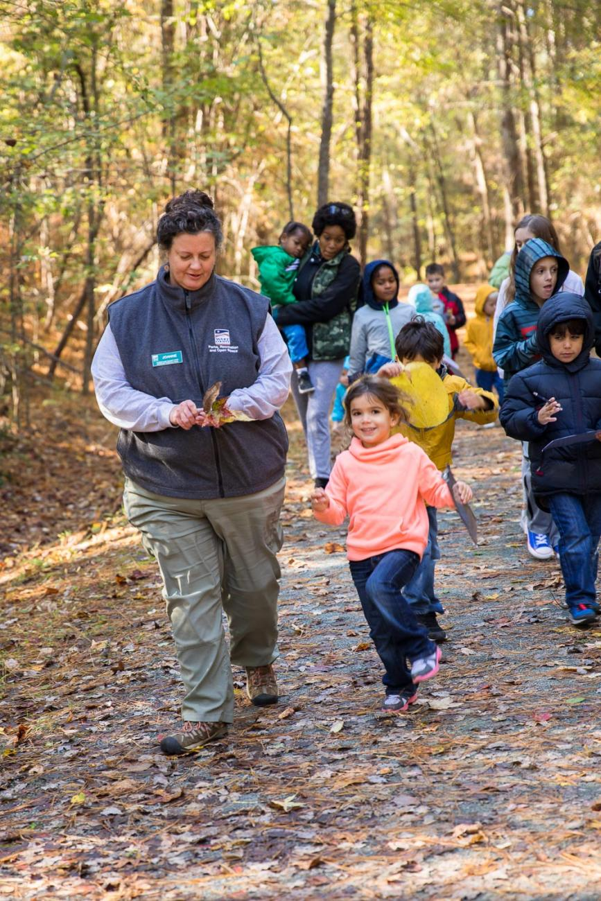 Photo of a park staff leading a program for families at the American Tobacco Trail