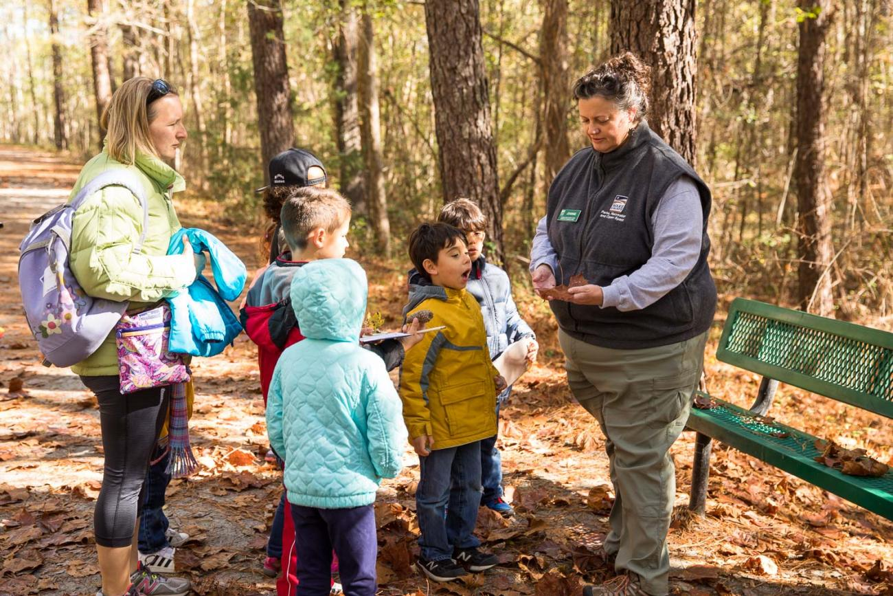 Photo of a park staff conducting a program for families at the American Tobacco Trail