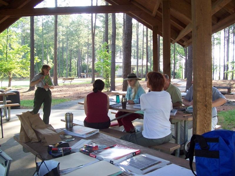Photo of adults listening to an instructor under one of the park's picnic shelters