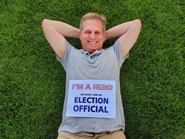 Election Official relaxing on green grass.