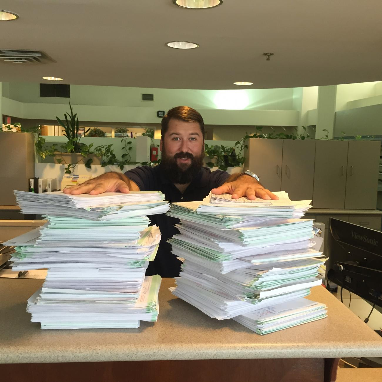 Male election worker with stacks of voter registration forms