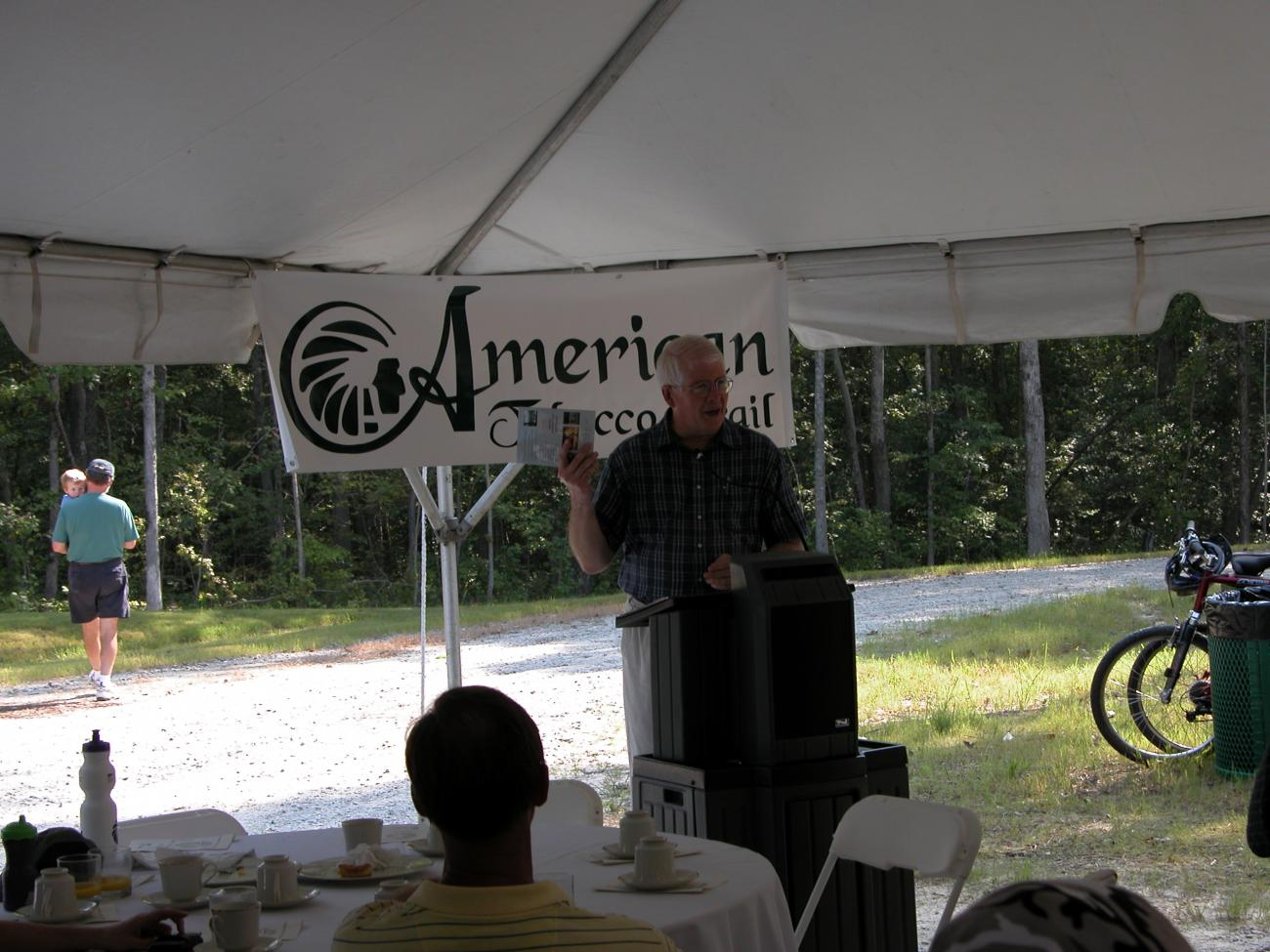 A photo from the Grand Opening celebration of the Wake County section of the American Tobacco Trail in 2003 - man speaking at podium