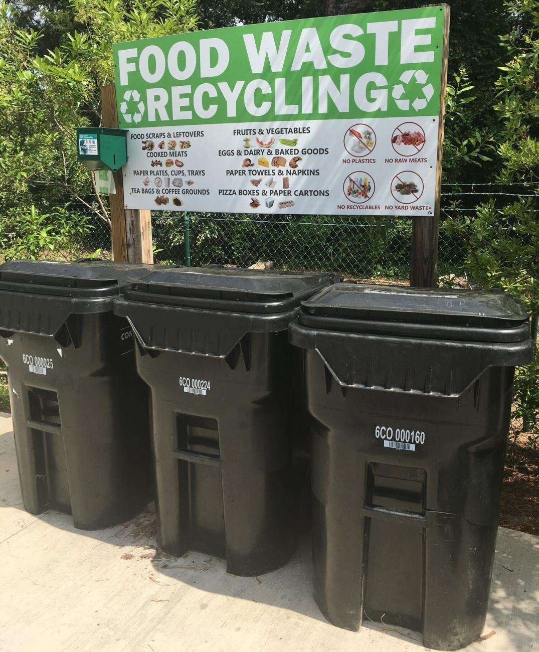 Three black carts in front of a sign that reads Food Waste Recycling.