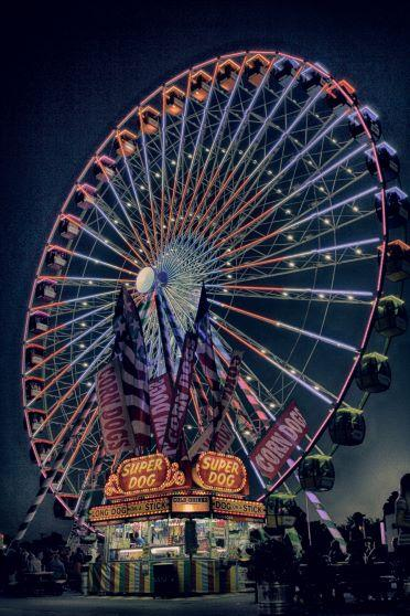 ferris wheel at night with hot dog stand