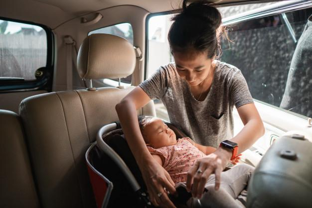 Mother securing a child in a passenger safety seat