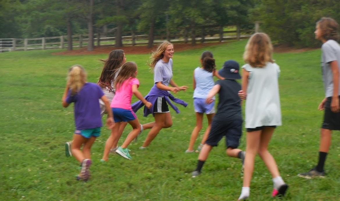 Kids run around in open field playing games