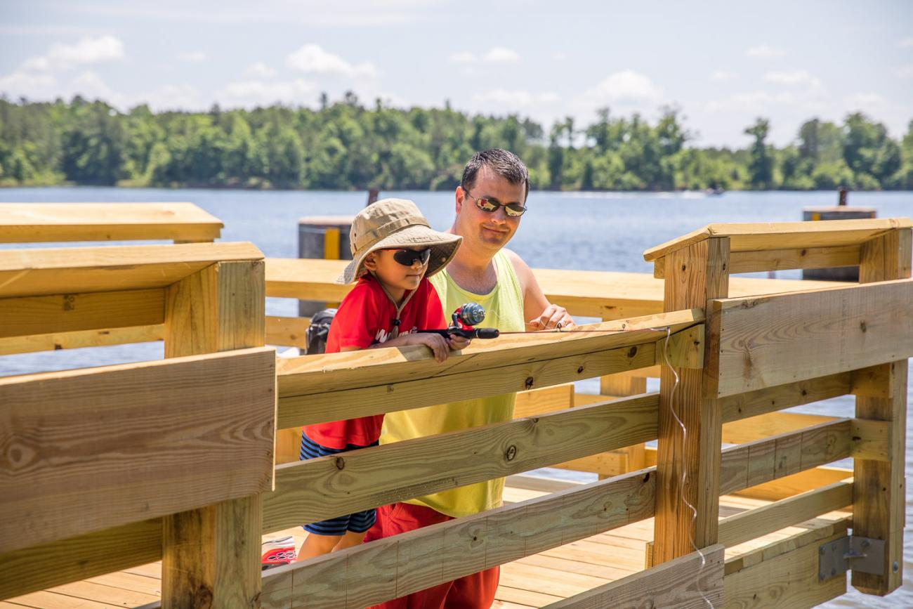 Photo of a father and son fishing together from the Fishing Pier at Harris Lake County Park