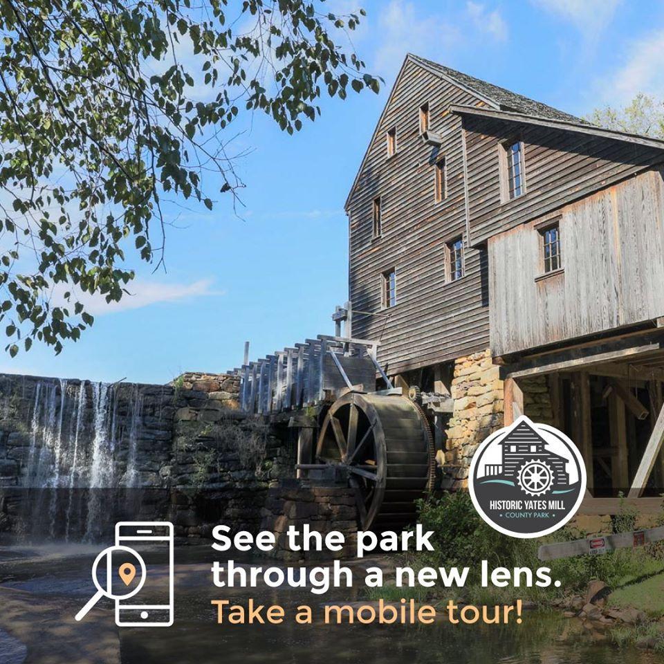 wooden mill building beside ponds edge promoting park mobile tour