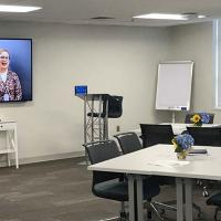 A picture of the Wake County Office Building Human Resources Training Room with tables & chairs, big screen monitor, and whiteboard