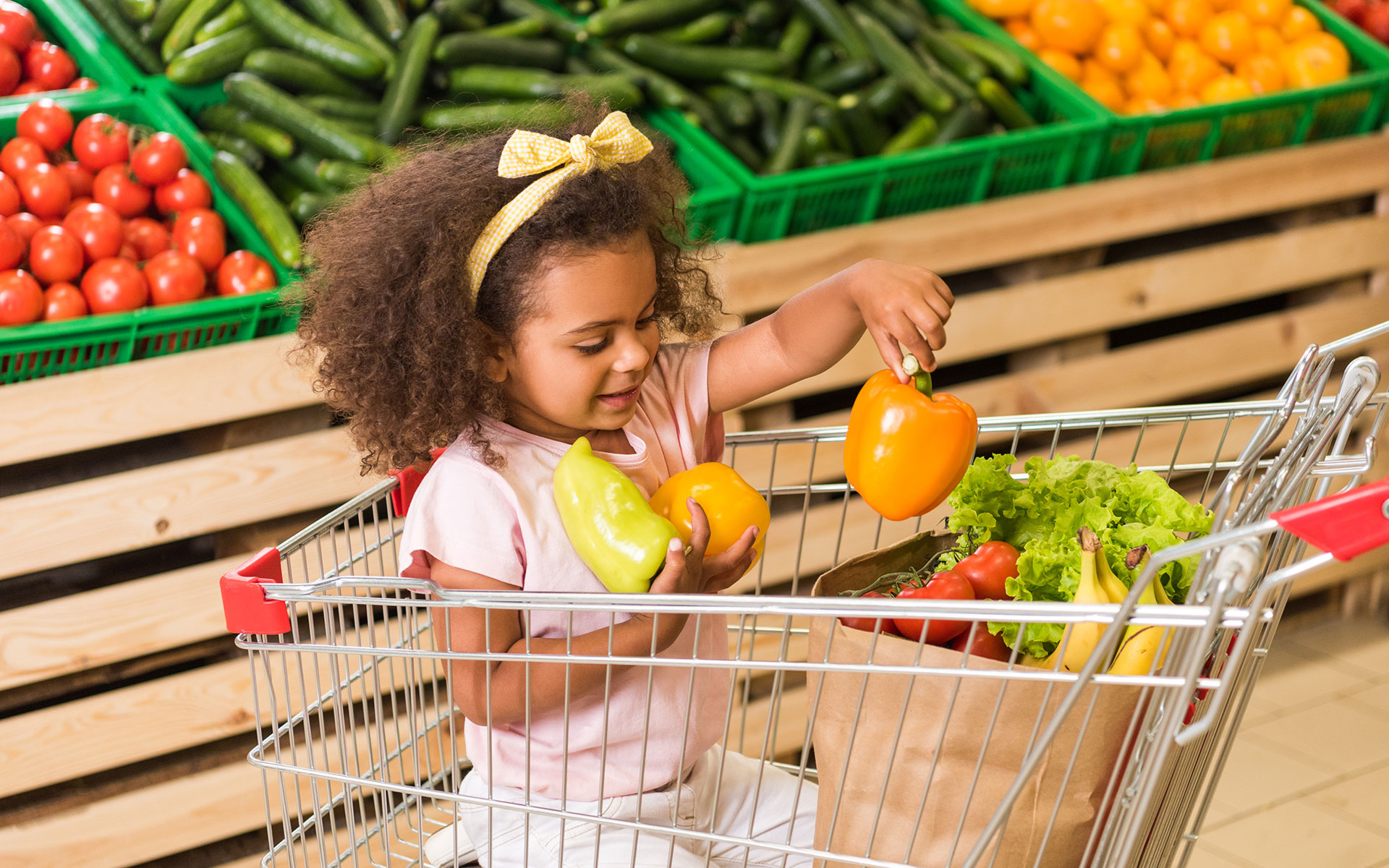 A child in a grocery cart holding three yellow bell peppers.