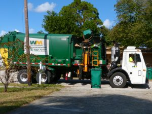 Waste Management garbage truck stopped in front of green curbside recyling bin.